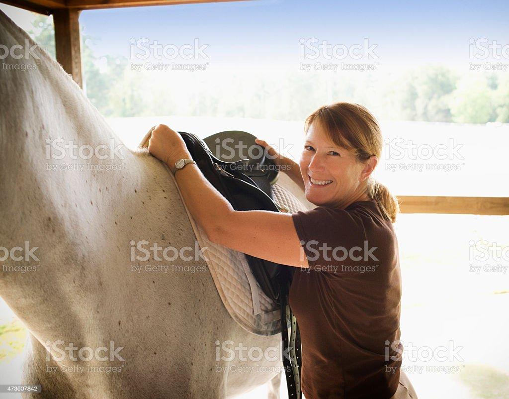 Female woman placing saddle on horse. stock photo