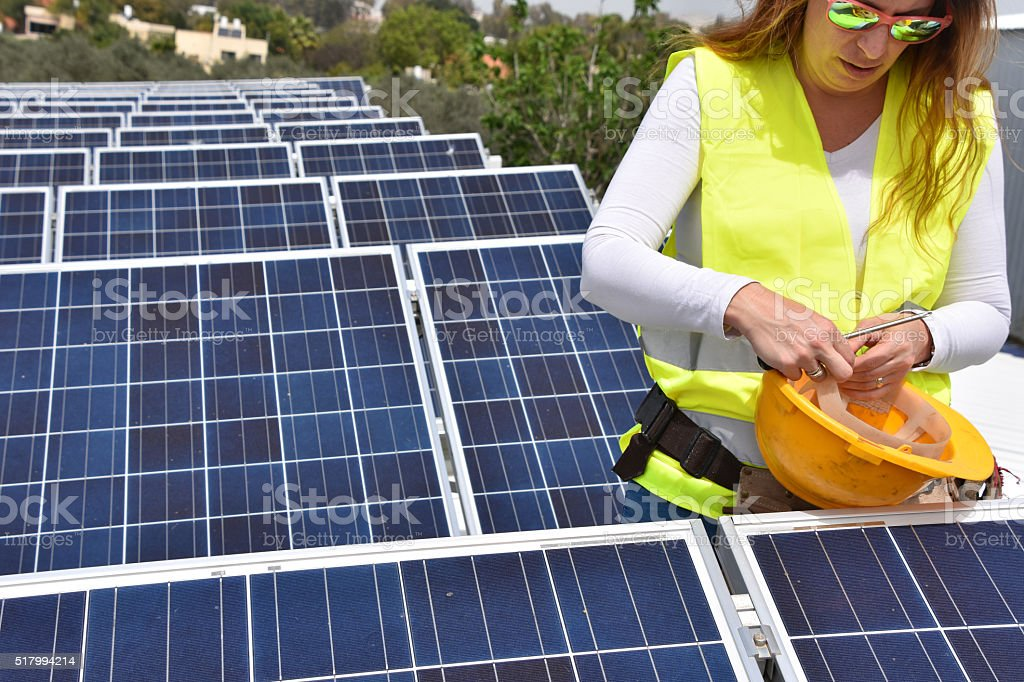 Female worker and solar panels stock photo