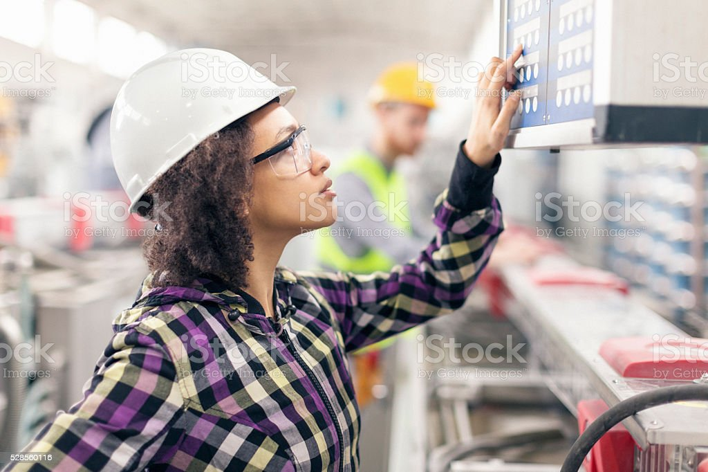 Female worker at control table in the factory stock photo