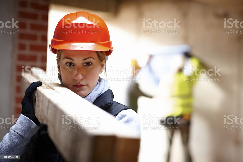 Female worker carrying wood at constructions site royalty-free stock photo