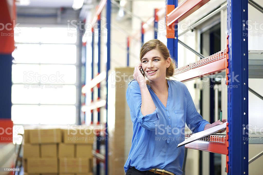 Female worker controlling stock and talking on cellphone in warehouse royalty-free stock photo