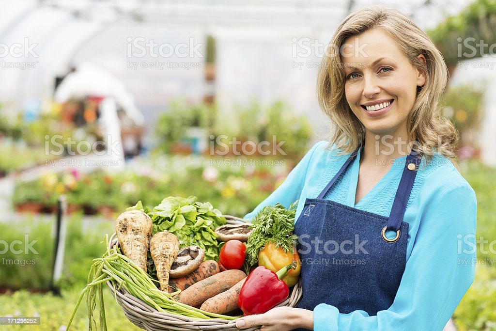 Female Worker Holding Basket Of Fresh Vegetables royalty-free stock photo