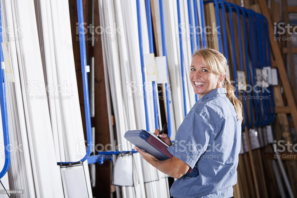 Female worker in building supply store taking inventory royalty-free stock photo