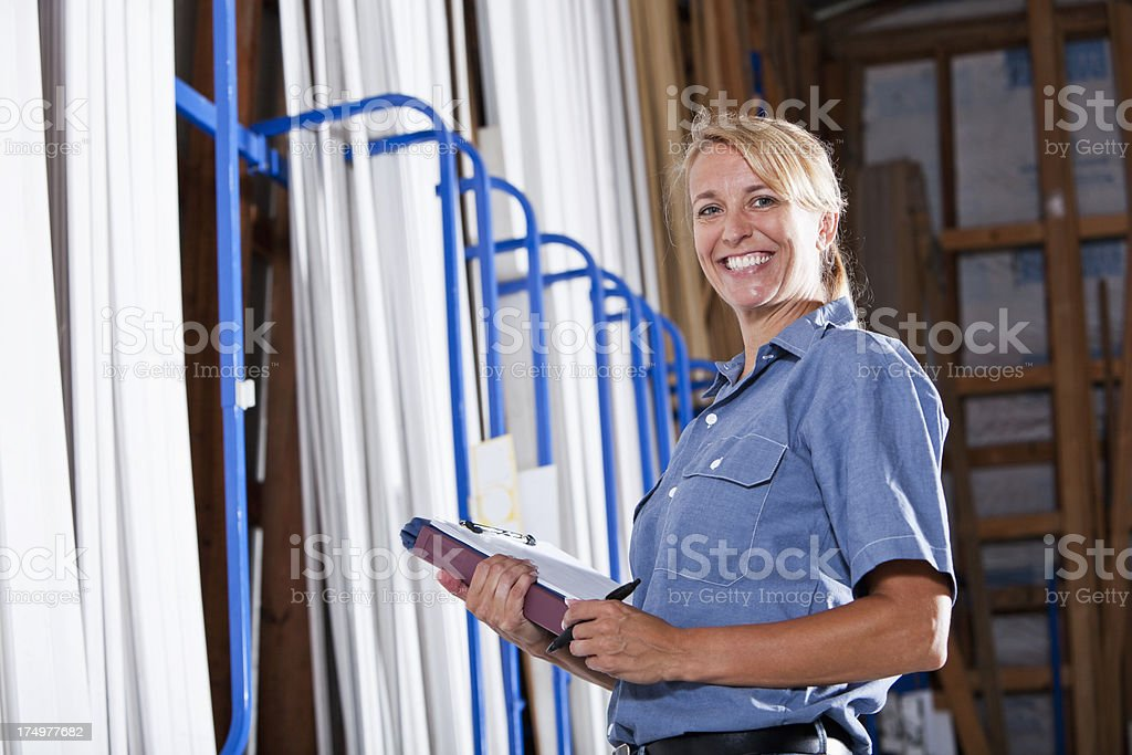 Female worker in building supply store taking inventory stock photo