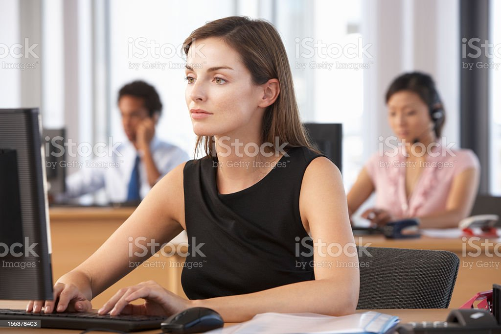 Female worker in busy office on desktop computer royalty-free stock photo