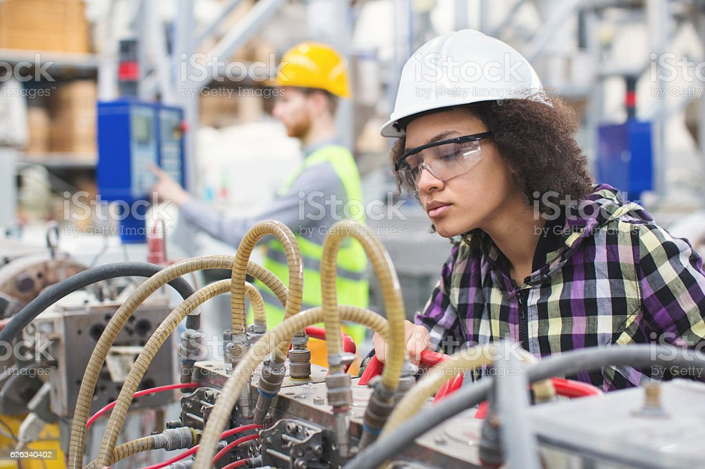 Female worker in the factory operating a machine stock photo