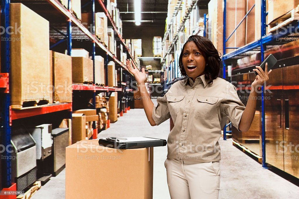 Female worker looking shocked in warehouse stock photo