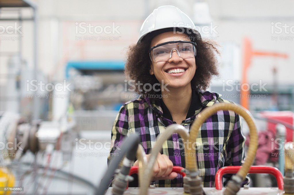 Female worker operating a machine and smiling for the camera stock photo