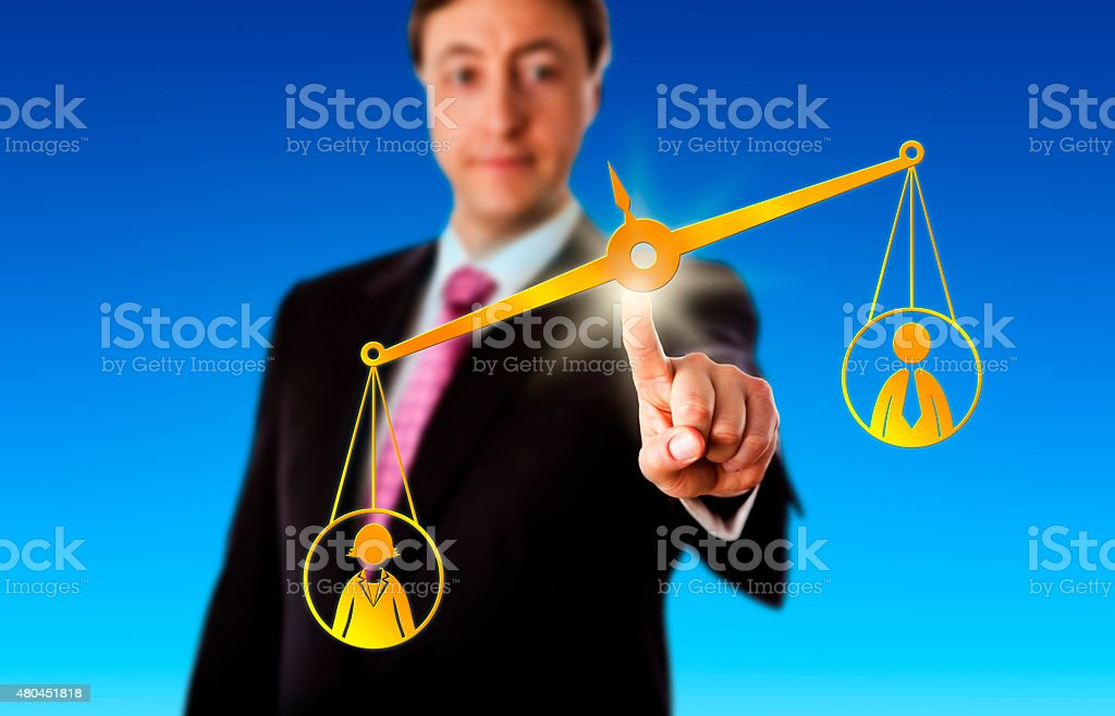 Female Worker Outbalancing A Male On A Scale stock photo