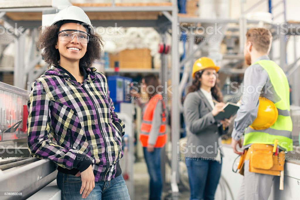 Female worker possing for the camera in the factory stock photo