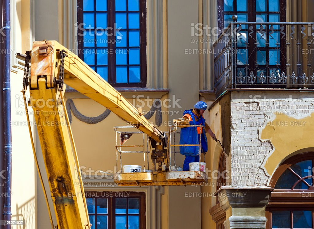 Female worker repairing old building wall royalty-free stock photo
