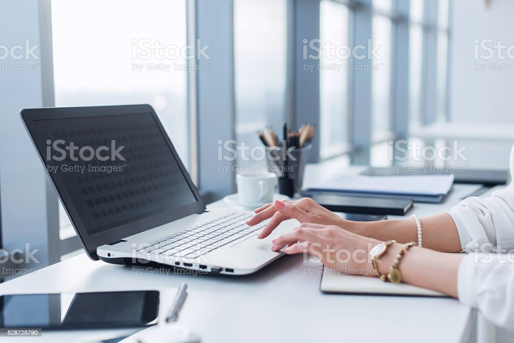 Female worker using laptop in office, working with new project stock photo