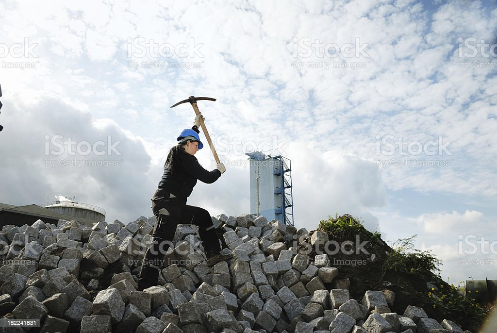 female worker using pickaxe royalty-free stock photo