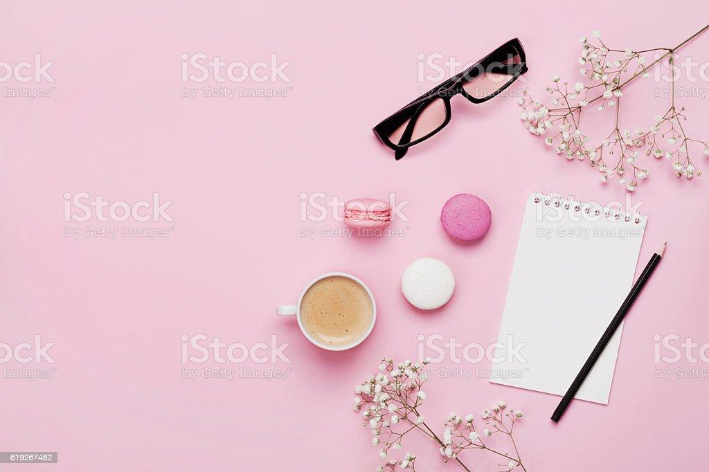 Female working desk. Coffee, macaroons, notebook, eyeglasses, flowers. Flat lay. stock photo