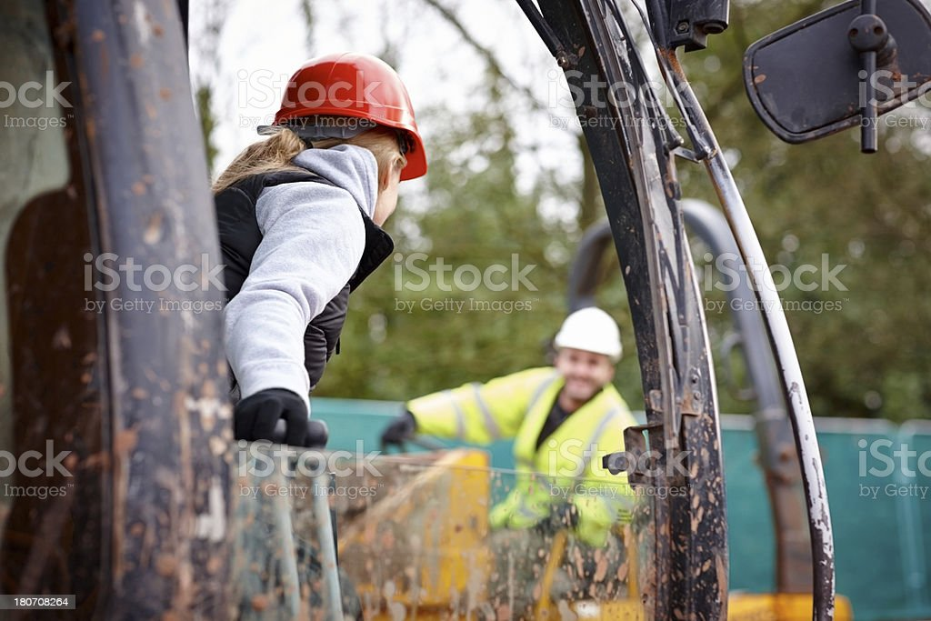 Female working driving excavator on work site royalty-free stock photo