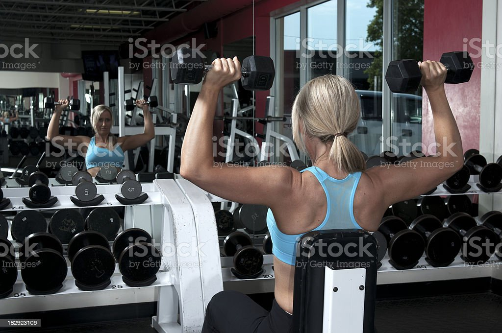 Female working out in a gym with barbells royalty-free stock photo
