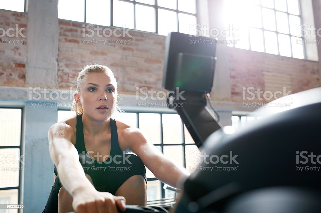 Female working out on a rowing machine at the gym stock photo