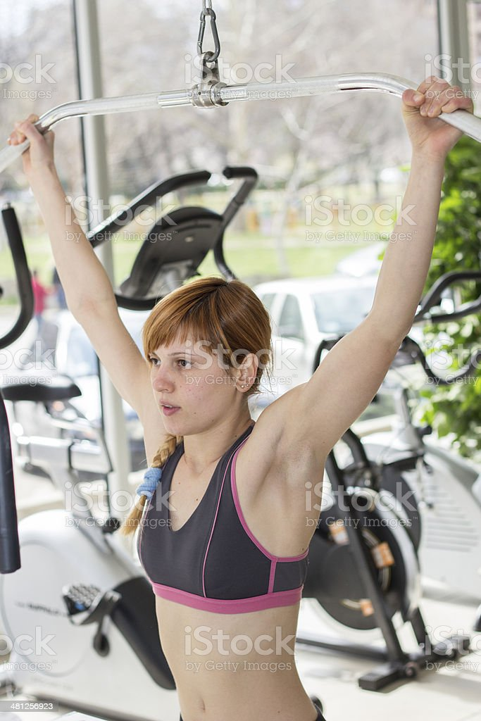 Female working out on lat pulldown machine royalty-free stock photo