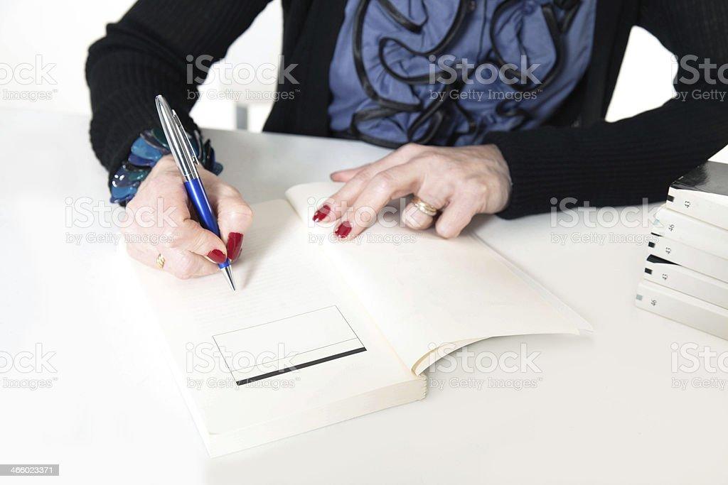 Female writer signing books stock photo