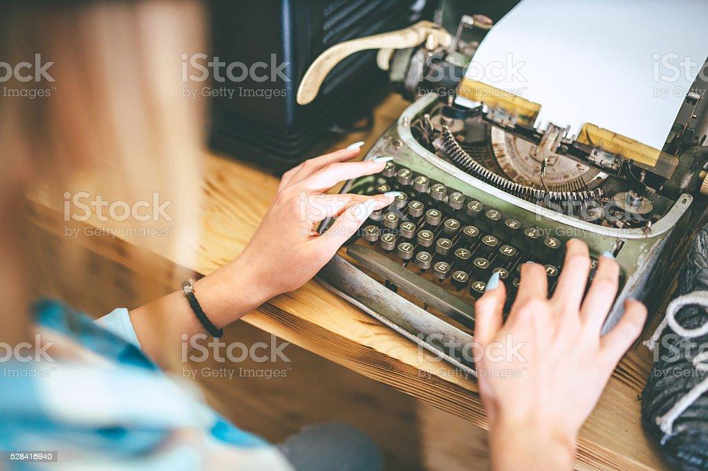 female writer typing on typewriter stock photo