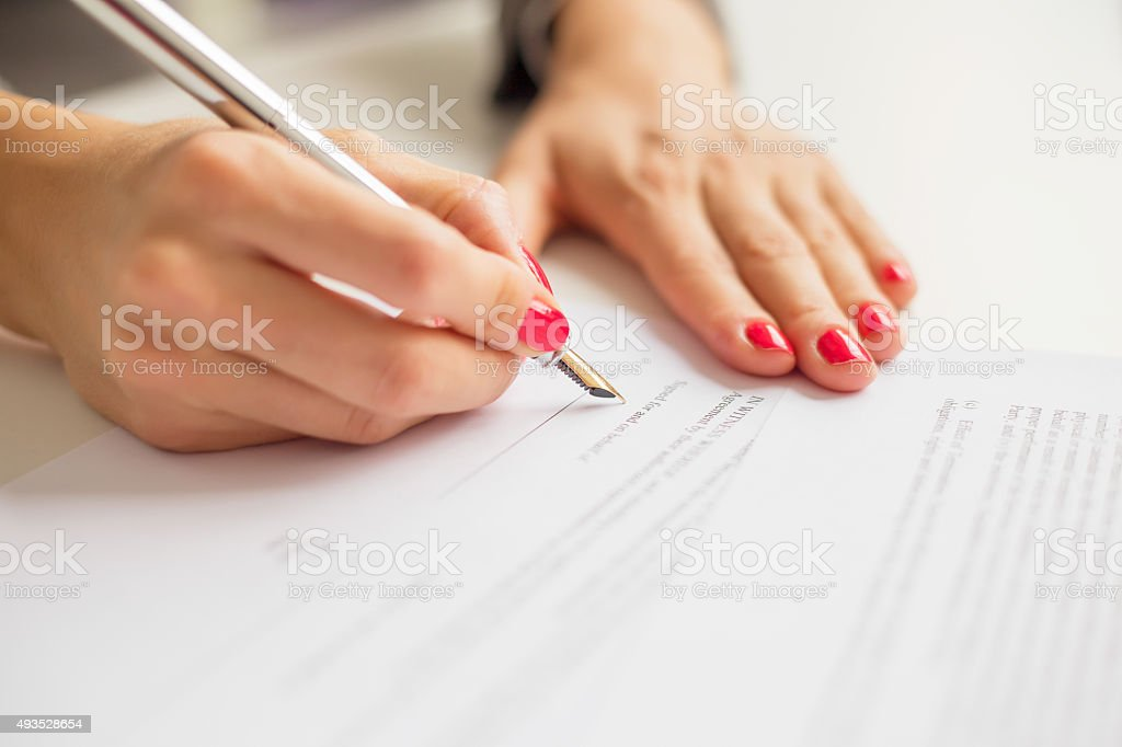 Female writing on paper stock photo