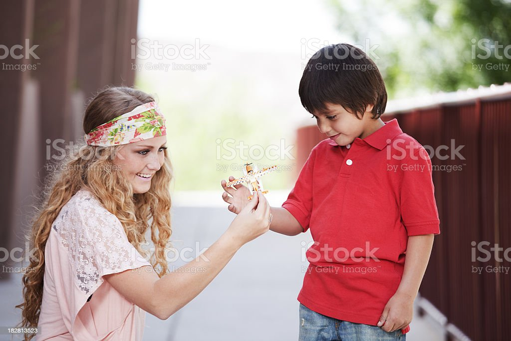 Female young adult playfully handing toy plane to little boy stock photo