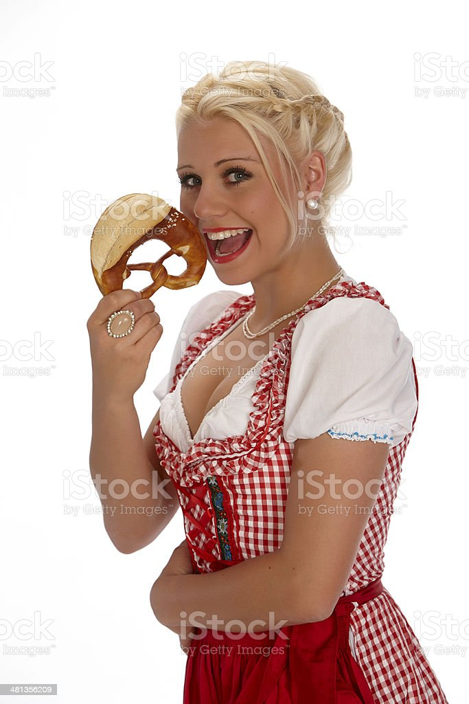 Female young blond with dirndl showing pretzel royalty-free stock photo