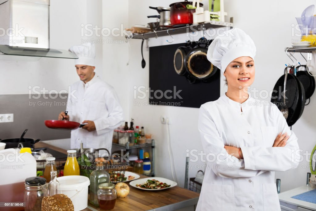 Female young cook wearing uniform working stock photo