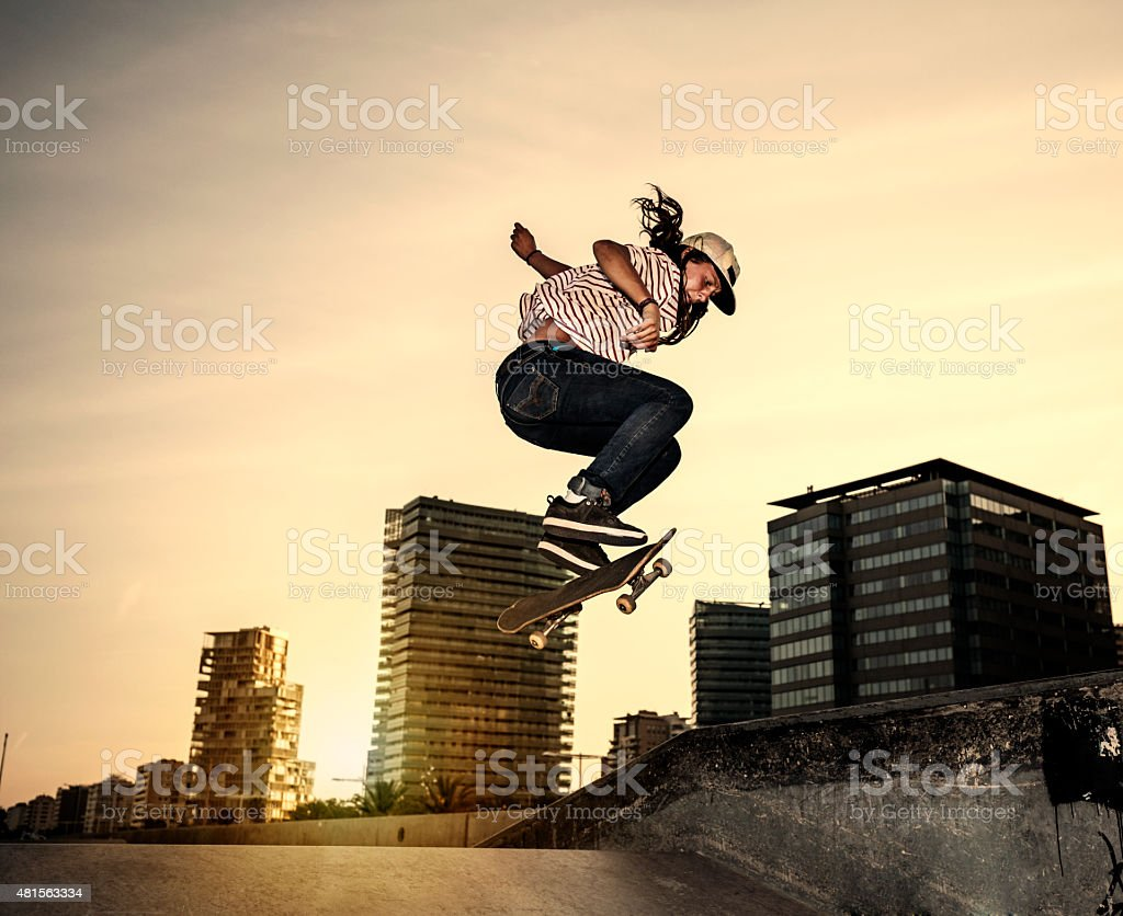 Female young skateboarder jumping in skatepark in the city stock photo