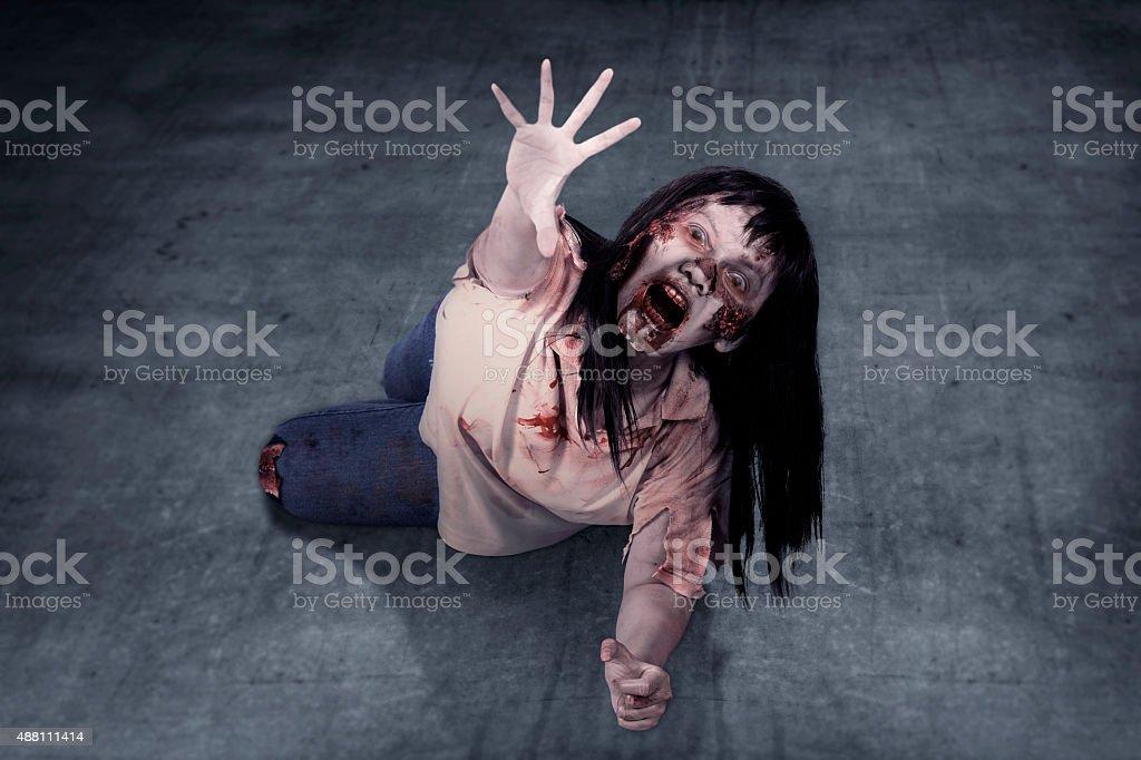 Female zombie crouching on the floor stock photo
