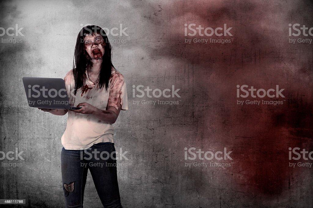 Female zombie holding laptop over grunge background stock photo