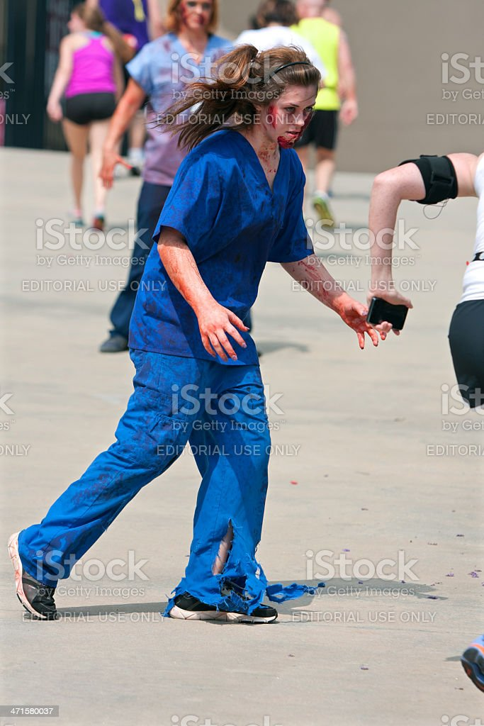 Female Zombie Nurse Chases Runner In 5K Race stock photo