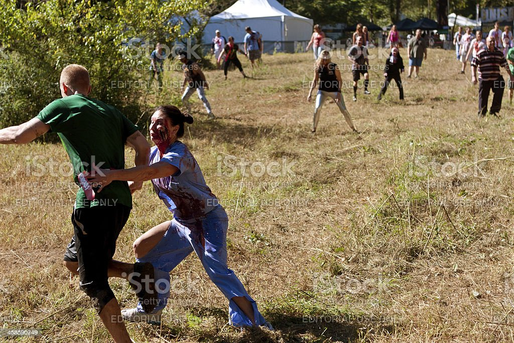 Female Zombie Nurse Chases Runner in Scary 5K Obstacle Race royalty-free stock photo