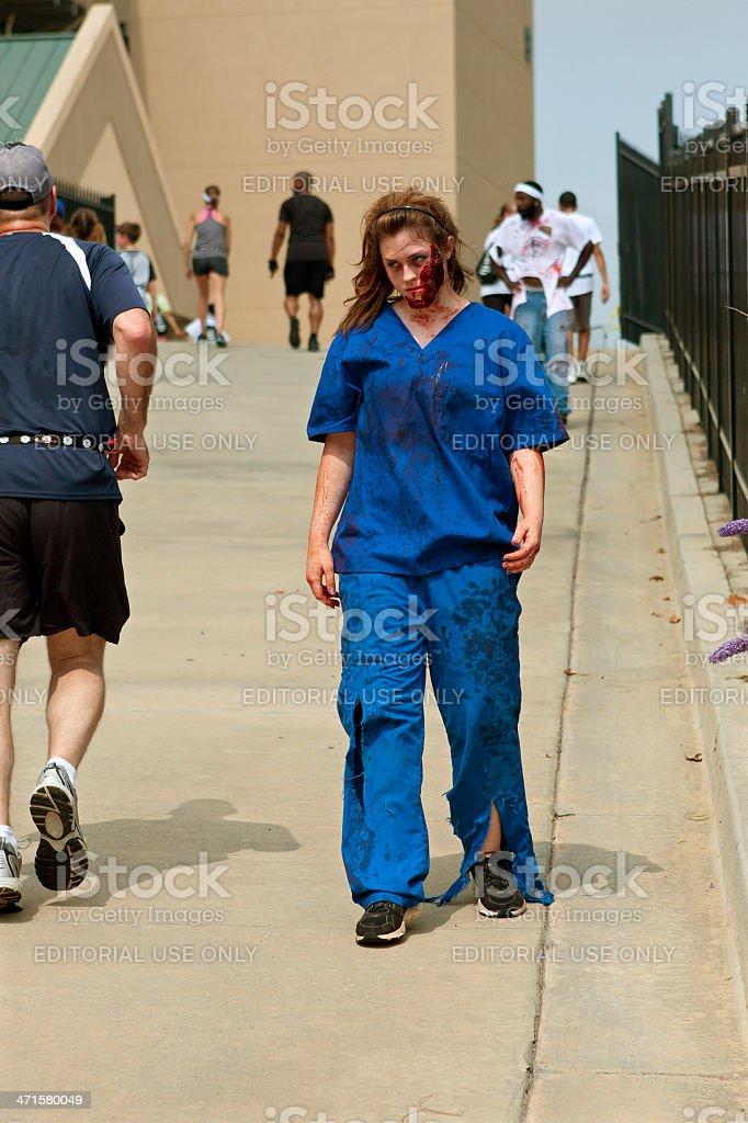 Female Zombie Nurse Skulks After Runners In 5K Run stock photo
