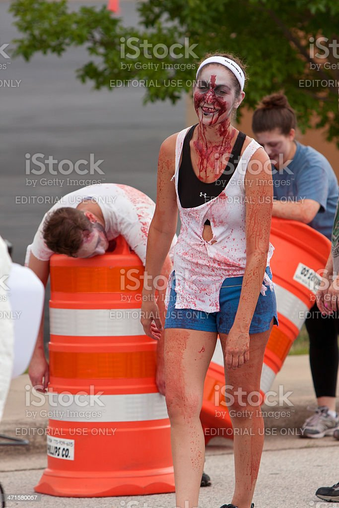 Female Zombie With Bloody Face Stalks Runners In 5K Race stock photo