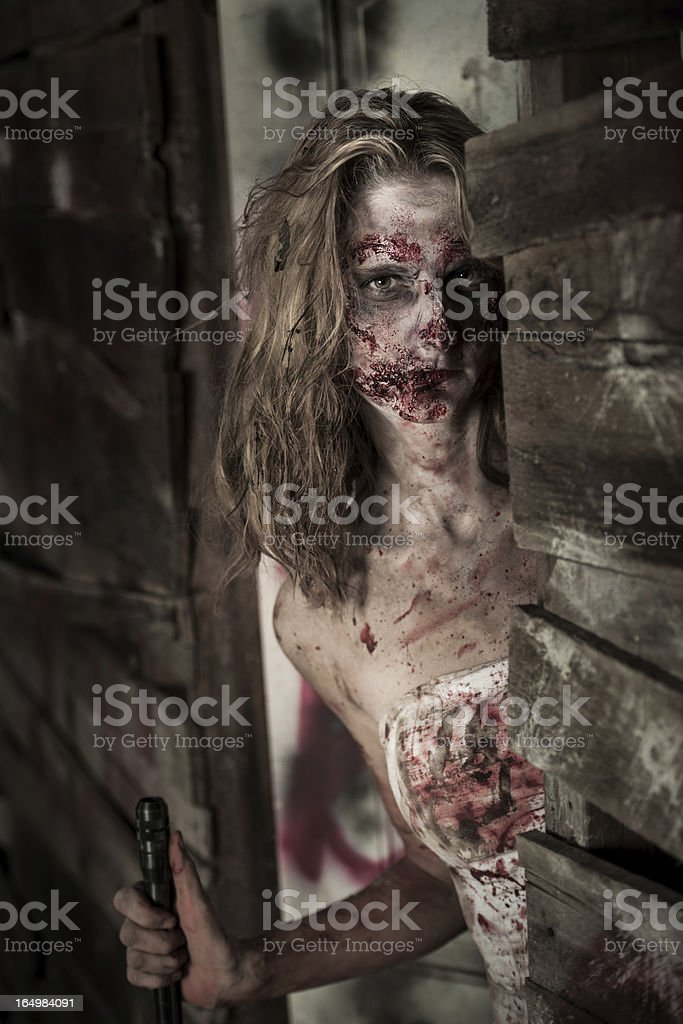 Female Zombie With Shotgun Peers Out To Front Porch stock photo