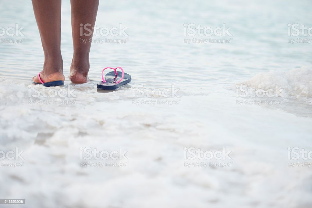 Female's foot on salt beach of Dead Sea. stock photo