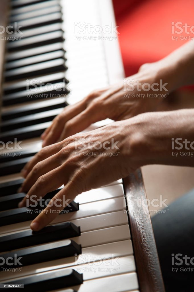 Females' hands playing piano high angle shot stock photo