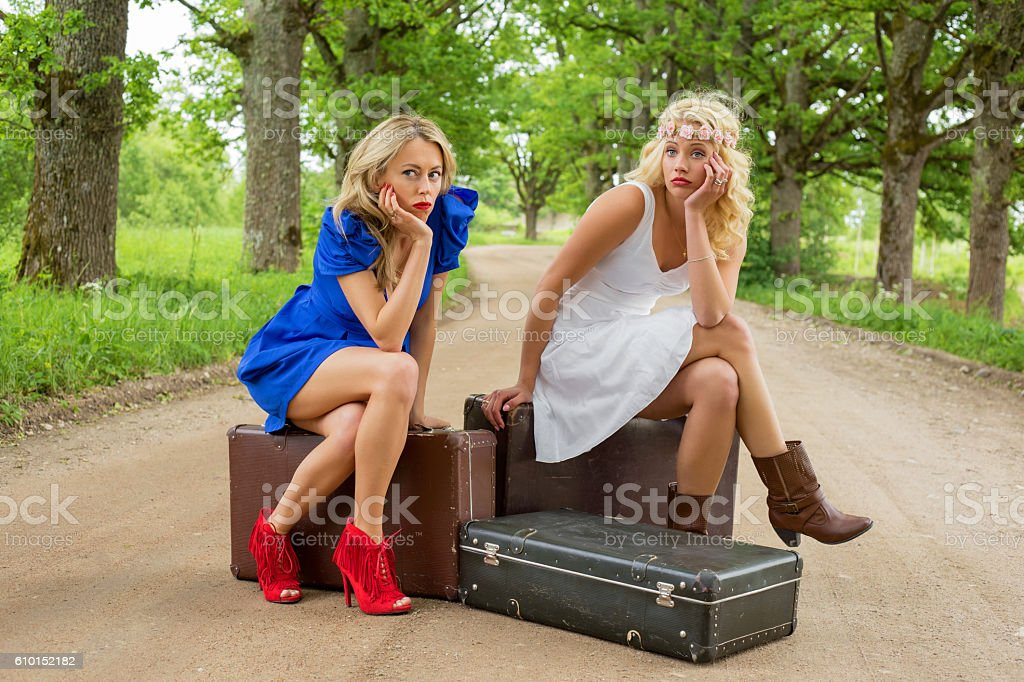 Females on dirt road sitting on the suitcases stock photo