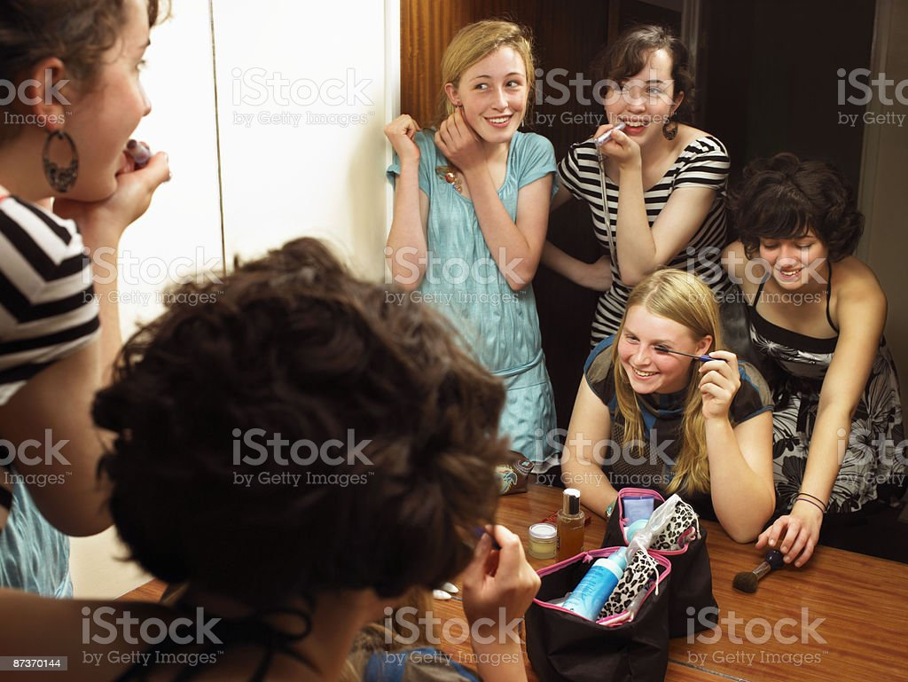 Females putting on make-up by mirror stock photo