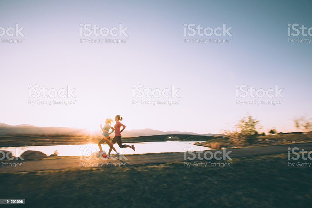Females Running on Path During Sunset in Utah stock photo