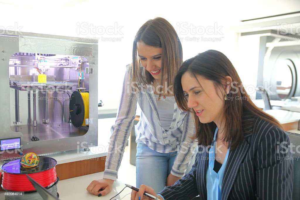 Females working in 3D printer Office stock photo