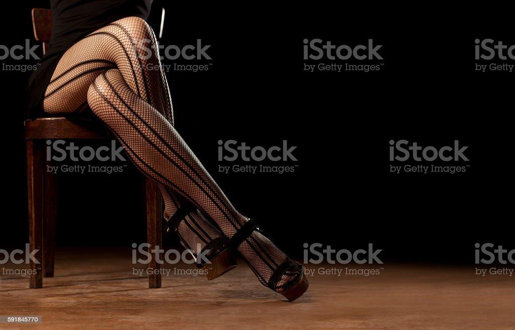 feminine crossed legs in fishnet stockings stock photo