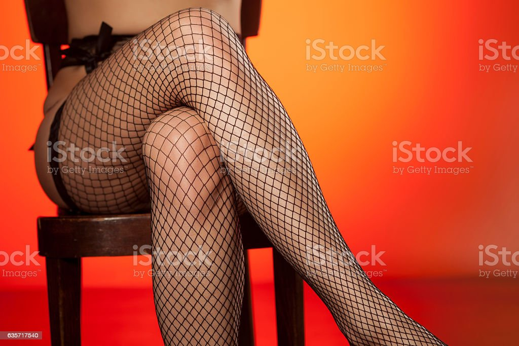 feminine crossed legs in fishnet stockings stock photo
