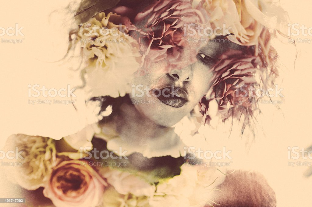 Feminine double exposure image of a woman and soft flowers stock photo