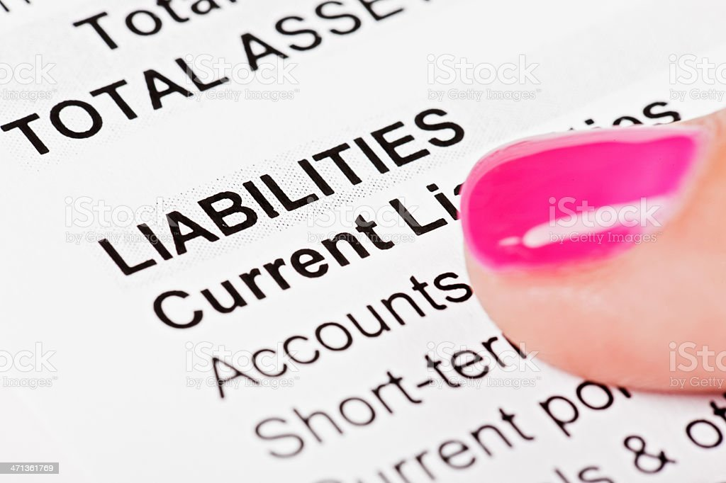 Feminine finger rests on Liabilities in financial document stock photo