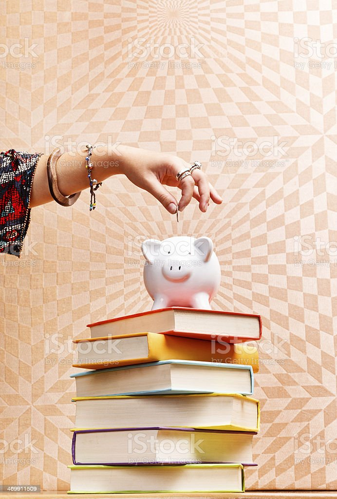 Feminine hand adds coin to piggybank on psychedelic background royalty-free stock photo