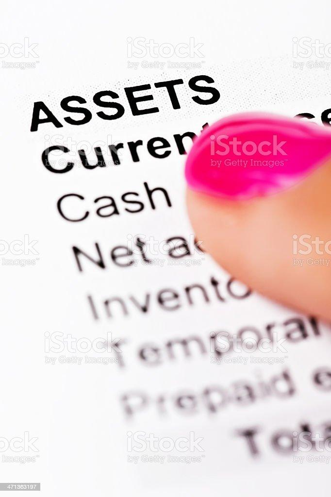 "Feminine hand points to word ""Assets"" on balance sheet stock photo"