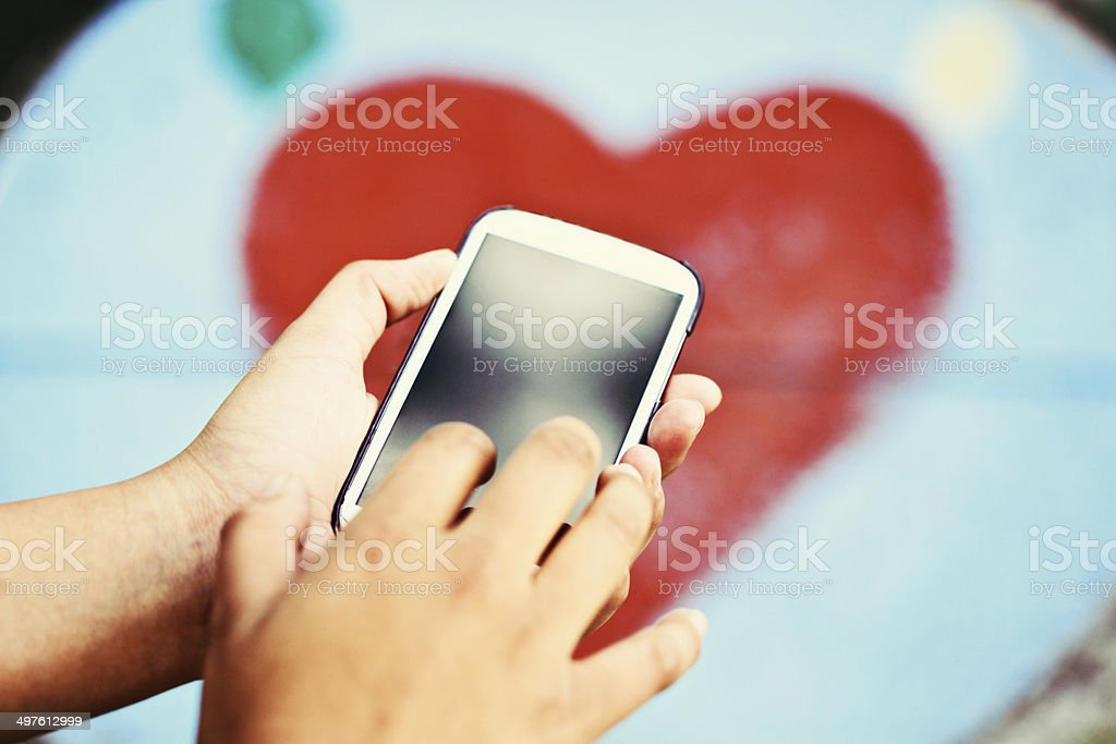 Feminine hand taps cellphone screen by heart. Valentine message? stock photo