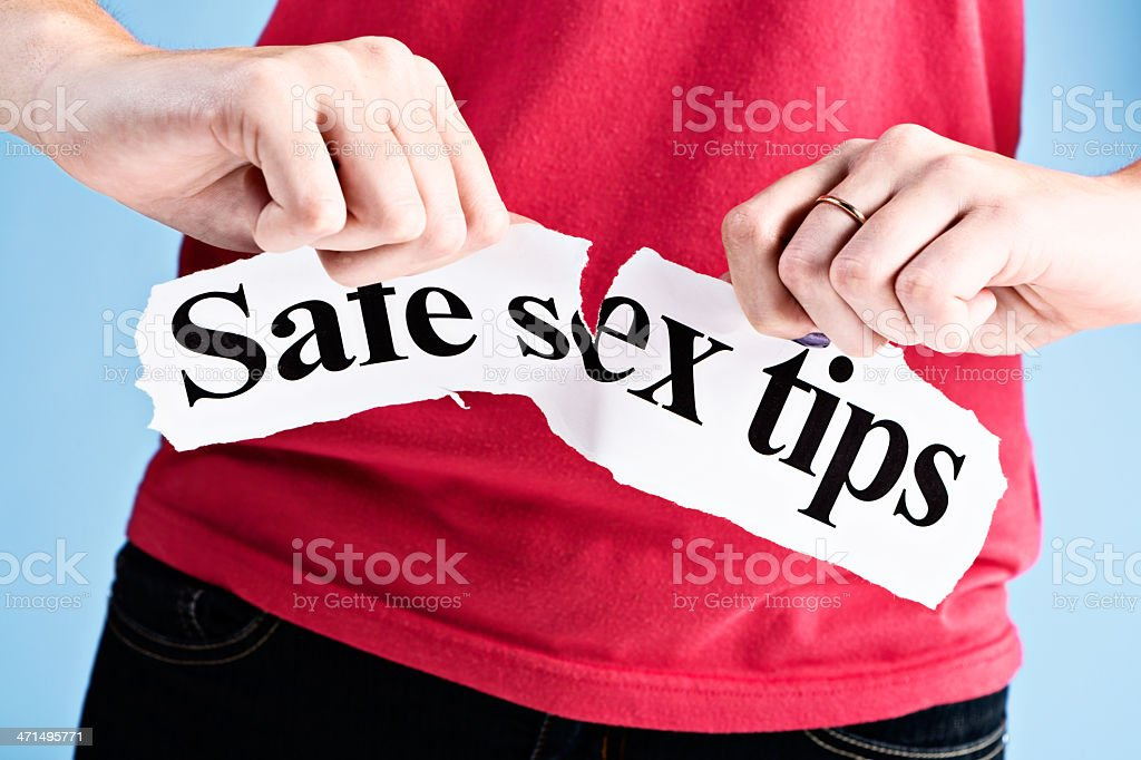 Feminine hand tears up Safe sex tips sign angrily royalty-free stock photo